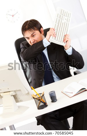 Angry  business man sitting at office desk and destroying computer using keyboard