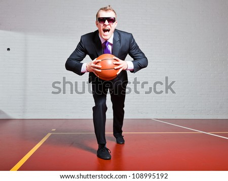 Angry business man with basketball. Wearing dark sunglasses. Good looking young man with short blond hair. Gym indoor. - stock photo