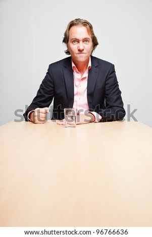 Angry business man with blond hair with glass of water sitting behind table in office isolated on white background - stock photo
