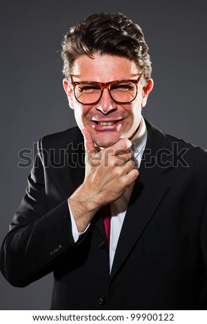 Angry business man with dark grey suit and red tie isolated on dark background. Wearing retro glasses. Studio shot.