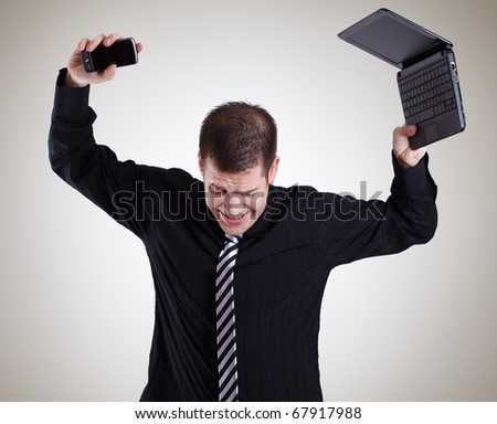 angry business man with laptop and cell phone - stock photo