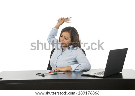 Angry business woman at her desk throwing pens against a white background - stock photo