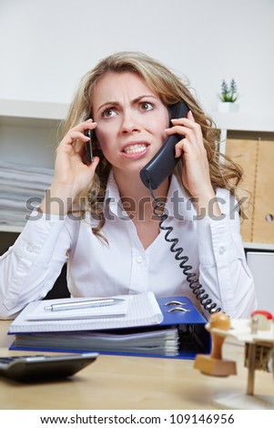 Angry business woman in her office on two phones at the same time - stock photo