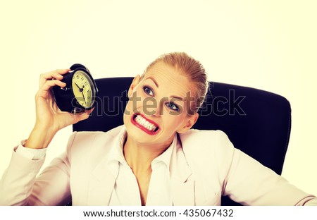 Angry business woman sitting behind the desk and shaking alarm clock - stock photo