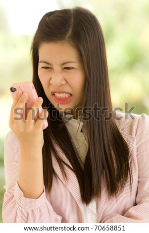 Angry business woman using cell phone. - stock photo