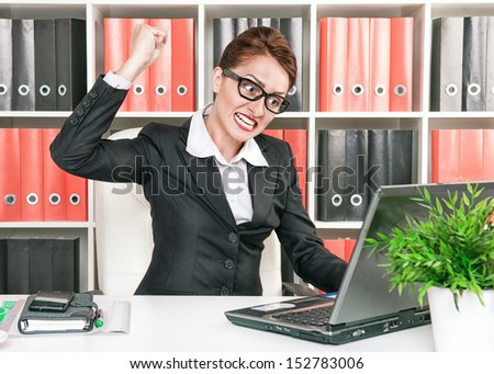 Angry business woman wants to break computer - stock photo