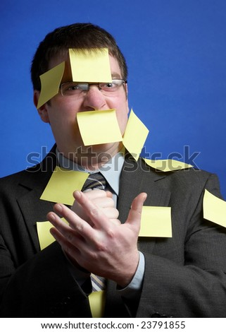 Angry businessman covered with yellow sticky notes - stock photo