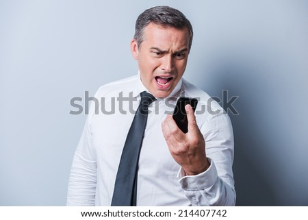 Angry businessman. Furious mature man in shirt and tie holding mobile phone and shouting at it while standing against grey background  - stock photo
