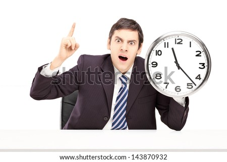Angry businessman holding a clock, isolated on white background