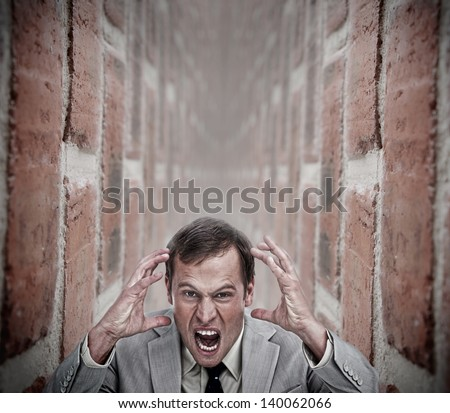 Angry businessman in a dead end in the middle of a bricks corridor - stock photo