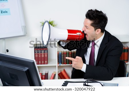 Angry businessman in an office, shouting on a megaphone - stock photo