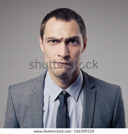 Angry Businessman On Gray Background - stock photo