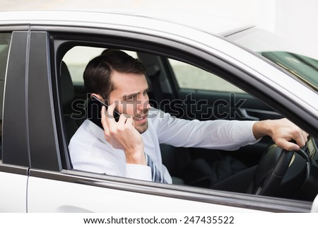 Angry businessman on the phone in his car - stock photo