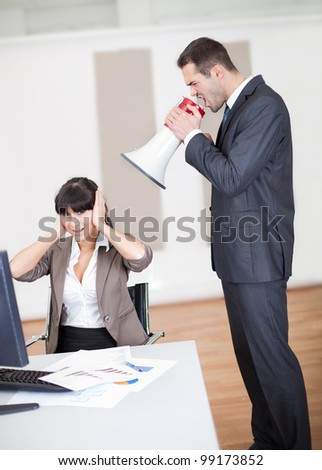Angry businessman screaming at employee at the office in megaphone - stock photo