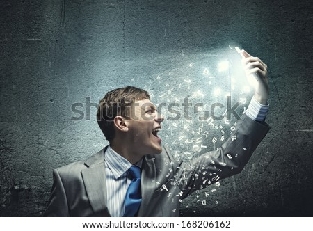Angry businessman screaming i to mobile furiously phone - stock photo