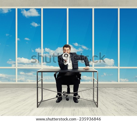 angry businessman screaming with megaphone and looking at camera in the light office with big windows - stock photo