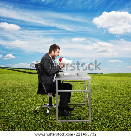 angry businessman screaming with megaphone and looking at laptop. photo at outdoor - stock photo