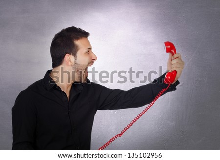 Angry Businessman shouting At Phone over irregular grey background - stock photo