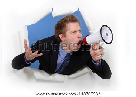 Angry businessman shouting through megaphone - stock photo