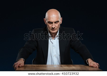 Angry businessman sitting at the table and looking at camera over black background - stock photo