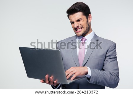 Angry businessman standing and using laptop over gray background - stock photo