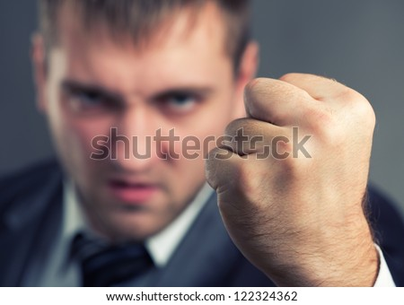 Angry businessman threaten with a fist - stock photo