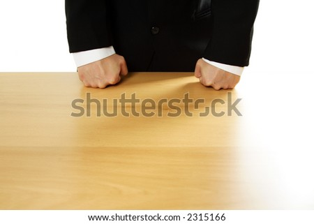 Angry businessman with both fists on the table