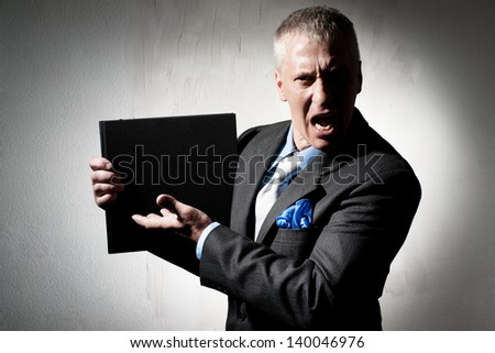 Angry businessman with business book - stock photo