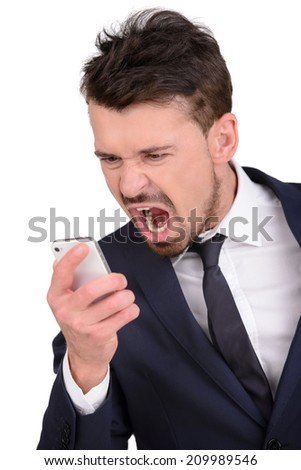 Angry businessman with mobile phone. Furious young businessman holding a mobile phone and pointing it while isolated on white