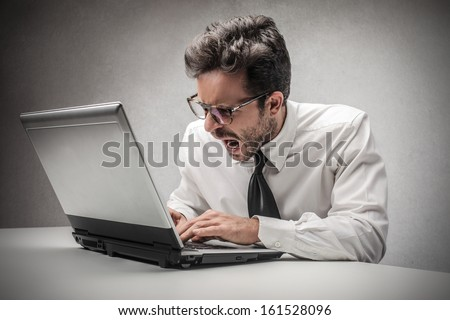 angry businessman working on the computer - stock photo