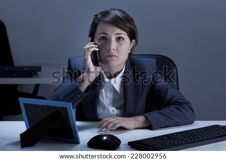 Angry businesswoman being on the phone in the office - stock photo