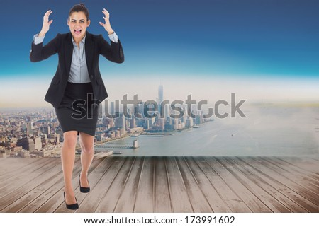Angry businesswoman gesturing against city projection on wall