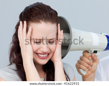 Angry businesswoman listening to a megaphone in the office