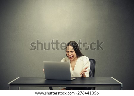 angry businesswoman looking at laptop and screaming over dark background - stock photo