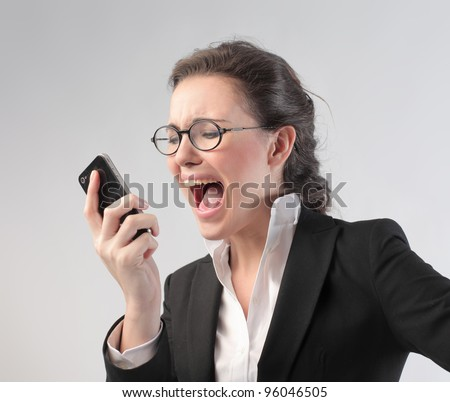 Angry businesswoman screaming on the mobile phone - stock photo