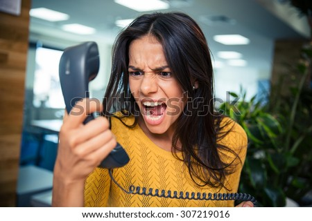 Angry businesswoman shouting on phone in office - stock photo