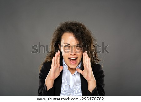 Angry businesswoman shouting, studio shot on gray background