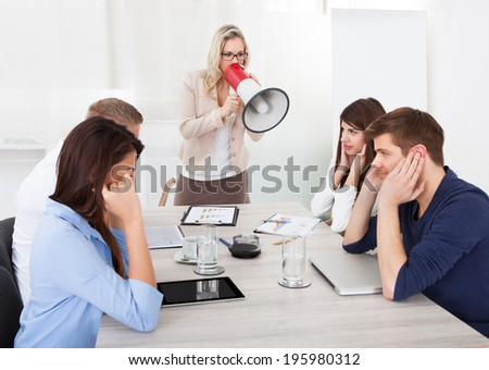 Angry businesswoman shouting through megaphone on colleagues in meeting at office - stock photo
