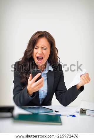 Angry businesswoman with phone in office. - stock photo
