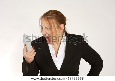 angry businesswoman yelling at wireless phone handset on white background - stock photo