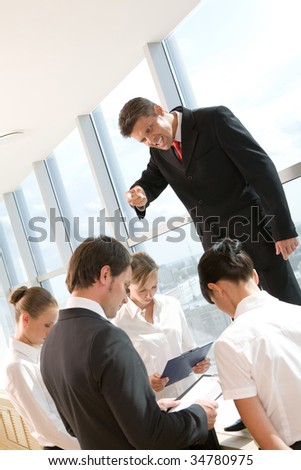 Angry ceo shouting at his employees surrounding him at meeting