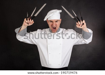 Angry chef with knifes on black background - stock photo