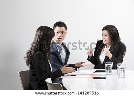 Angry Chinese business man shouting at his colleague in a business meeting - stock photo