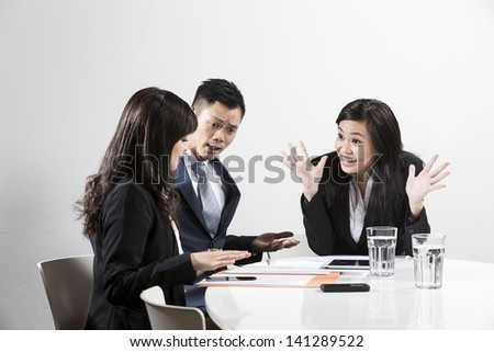 Angry Chinese businesswoman shouting at her colleagues in a business meeting - stock photo