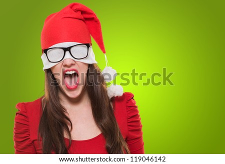 angry christmas woman with a hat and glasses covering her eyes against a green background