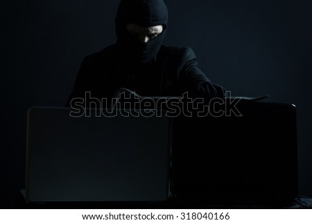 Angry computer hacker in suit stealing data from laptop with crowbar in front of black background - stock photo