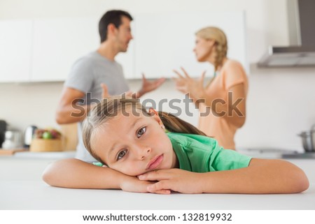 Angry couple arguing behind a sad girl at home - stock photo