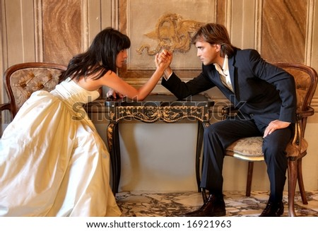Angry couple battling it off with some arm wrestling - stock photo