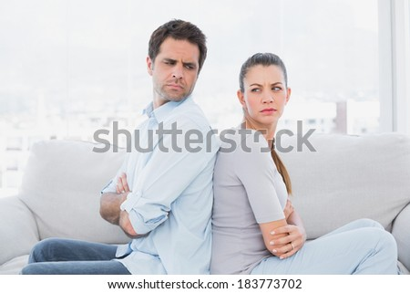 Angry couple sitting back to back on the couch at home in the living room - stock photo