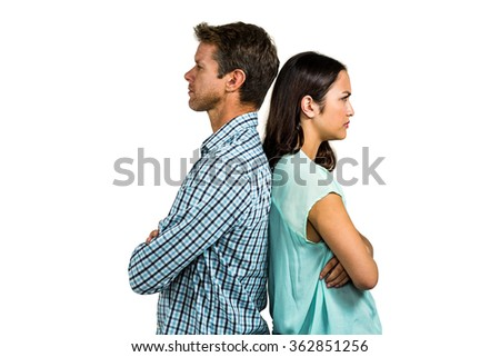 Angry couple standing back to back against white background - stock photo